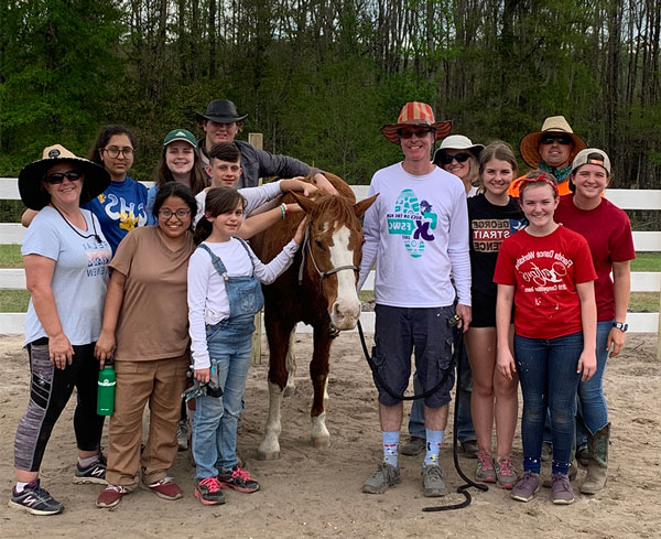 Members of the First United Methodist Youth Group learn about horses on a nearby farm